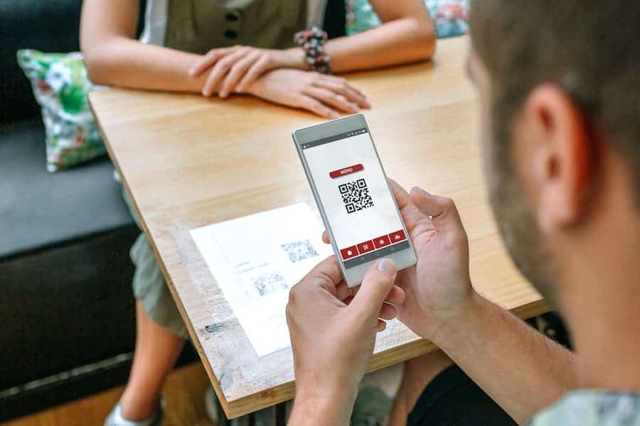 person paying with qr code menu